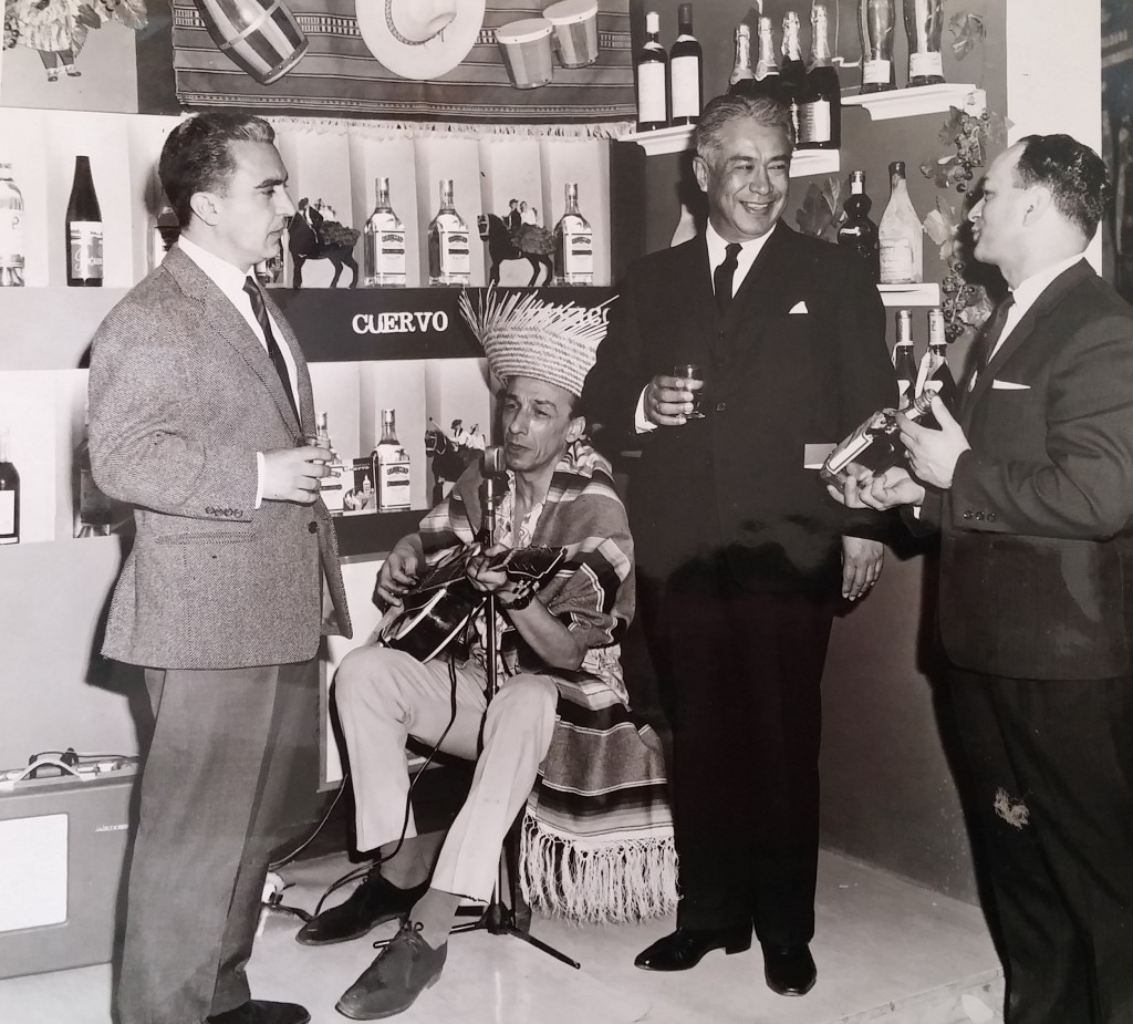 Mexican guitarist Eddie Dushan (second from left) sings in his native Spanish for Senor Antonio Armendariz, the Mexican Ambassador to the UK on the Capital Wine Agencies stand at a trade fair with CEO, Stan Sklar (right). April 18th, 1064
